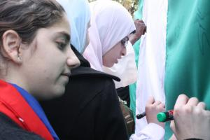 Students writing on the Nigerian flag (Photo:  Adyan)